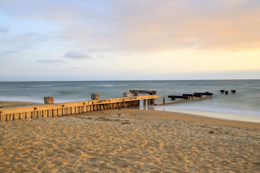 The remains of an old pier at dusk Pier Beach Beauty In Nature Cloud - Sky Coastline Holiday Horizon Horizon Over Water Land Motion Nature No People Outdoors Sand Scenics - Nature Sea Sky Tranquil Scene Tranquility Vacations Water Wooden Post