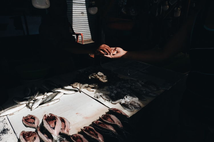 Cropped hand of person giving money to vendor while buying fish at market