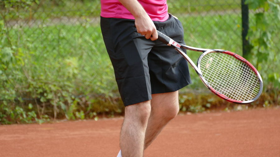 Adult Adults Only Close-up Competition Competitive Sport Court Day Holding Human Body Part Low Section Midsection Motion One Person Outdoors People Playing Racket Racket Sport Sport Sports Clothing Sportsman Standing Tennis Tennis Ball Tennis Racket