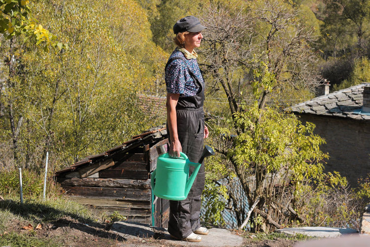 Side view of woman holding watering can while standing against trees