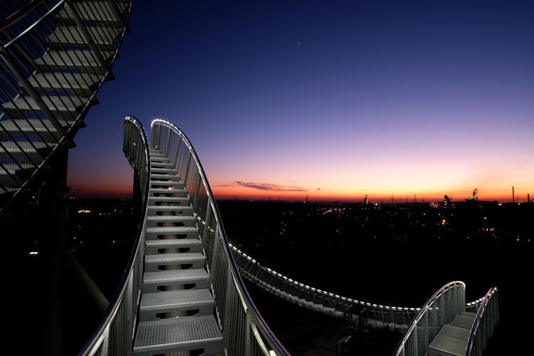 This sculpture Tiger and Turtle - Magic Mountain, by German artists Heike Mutter and Ulrich Genth, is modelled on a roller coaster. Visitors are able to walk the steps. Architecture FUJIFILM X-T2 Fujifilm_xseries Bridge - Man Made Structure Building Exterior Business Finance And Industry City Decision Decisions Dusk Outdoors Sky Staircase Staircases Steps Steps Sunset The Week Of Eyeem Tourism Travel Travel Destinations Two Ways Up Urban Skyline Vacations HUAWEI Photo Award: After Dark