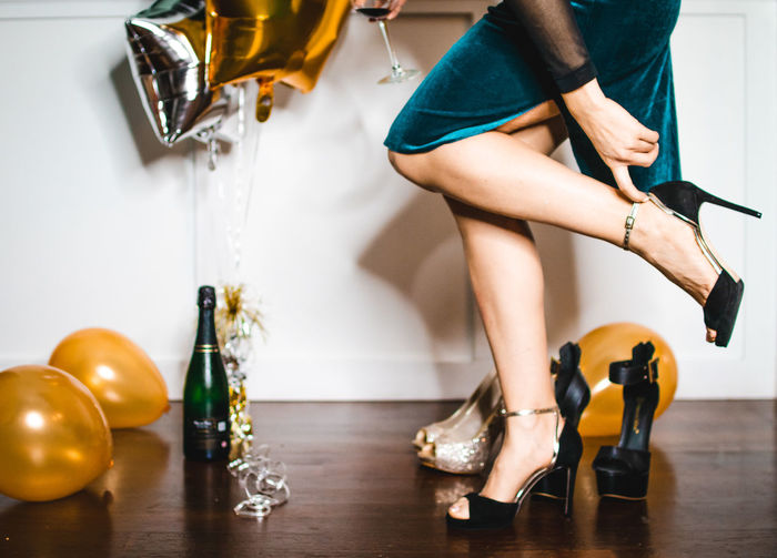 woman adjusting her high heel shoe at a fancy new years eve party Low Section One Person Human Leg Shoe Indoors  High Heels Women Adult Fashion Human Body Part Real People Lifestyles Body Part Flooring Leisure Activity Home Interior Home Casual Clothing Human Limb Party Balloons Champagne Getting Ready New Years Eve Fancy