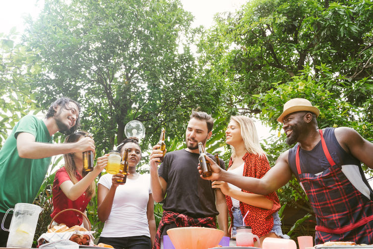 Group of friends toasting beers outdoors. Party people drinks toast celebration. Beer Beer - Alcohol Beer Glass Beers Drink Bottle Celebration Celebrating Celebrate BBQ BBQ Time Outdoors Park Garden Barbecue Barbecue Grill Grill Grilled Grilling African African Ethnicity Asian  Friendship Group Of People Food And Drink Tree Smiling Refreshment Plant Alcohol Togetherness Casual Clothing Leisure Activity Men Young Adult Young Men Happiness Adult Women Glass Drinking
