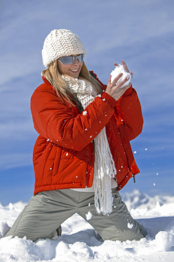 Smiling Woman Wearing Warm Clothing Kneeling On Snow During Winter