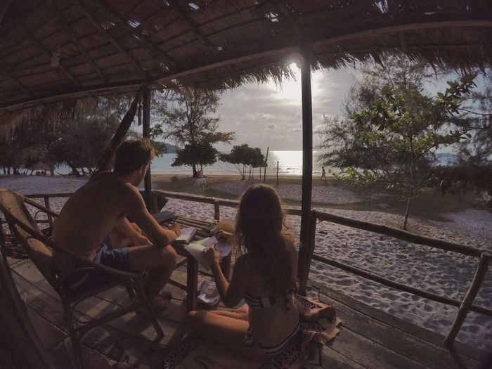 High angle view couple sitting on beach terrace