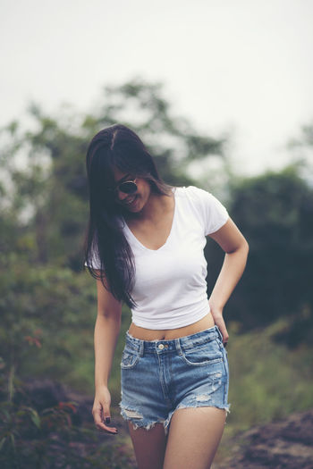 Young woman wearing sunglasses standing on land