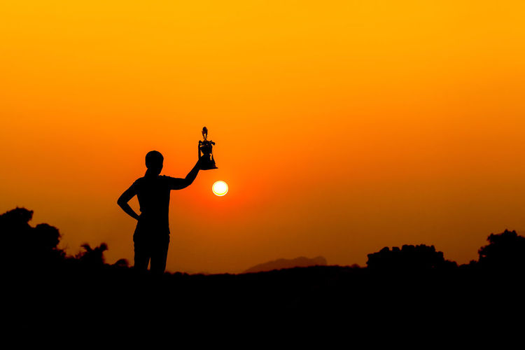 Silhouette woman holding trophy while standing on land against sky during sunset