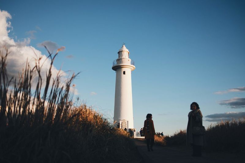 People by lighthouse against sky