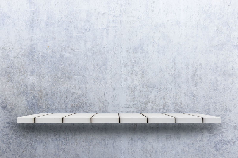 High angle view of empty table against white wall