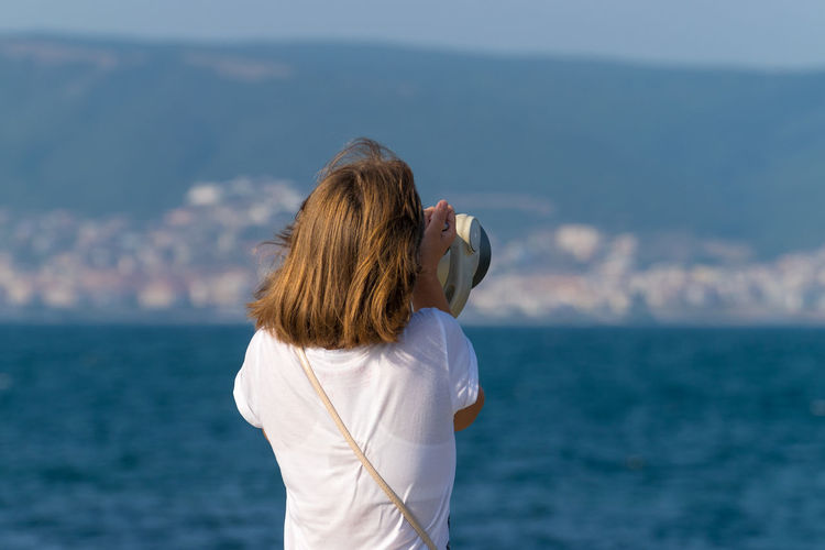 Rear view of woman looking at sea through coin-operated binoculars against sky
