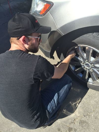 High Angle View Of Young Man Inflating Car Tire At Gas Station