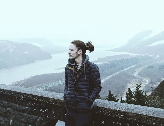 Young man standing against mountain and river during winter