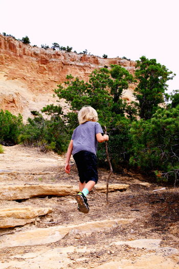 Rear view of boy hiking on rock formation at dinosaur national monument