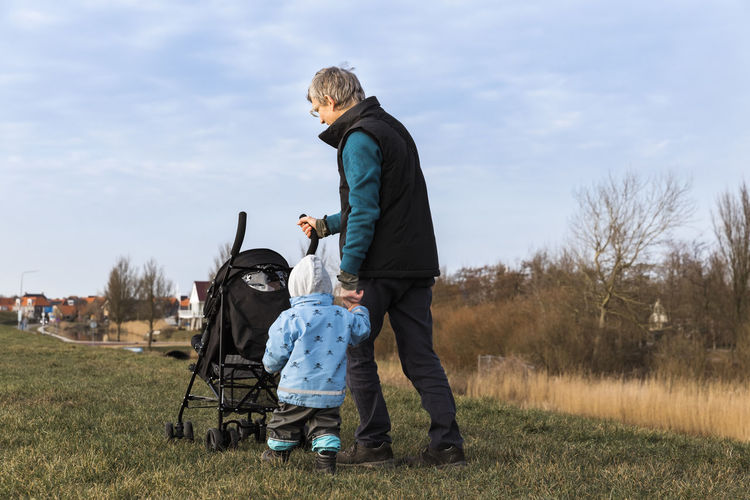 Rear View Full Length Of Man Walking With Granddaughter On Field