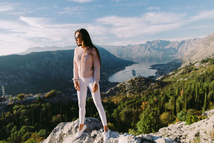 Full length of young woman standing on rock against sky