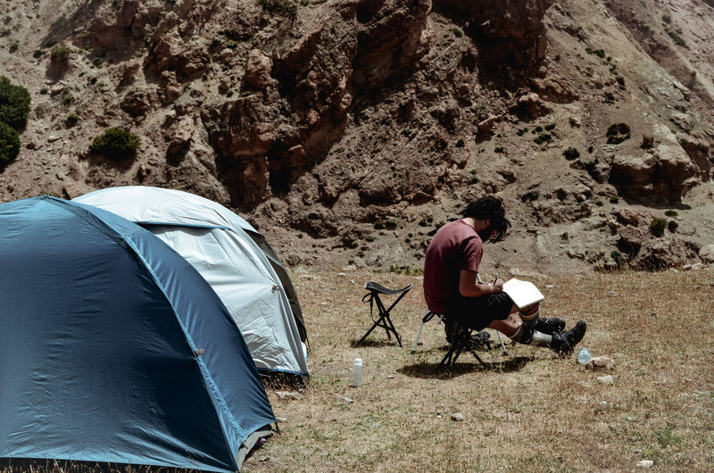 High angle view of man sitting on tent