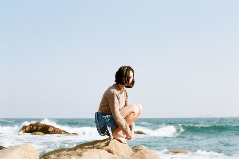 Side view of a woman sitting on beach