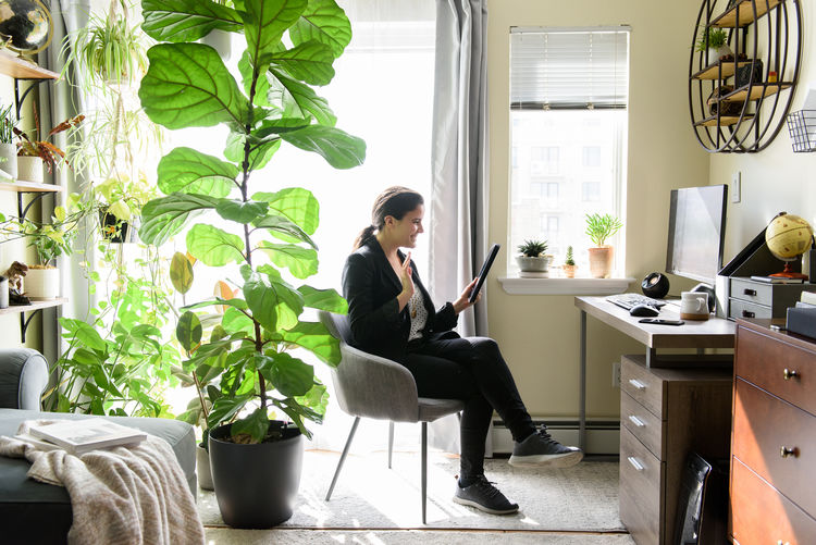 Woman sitting on chair by potted plant on table