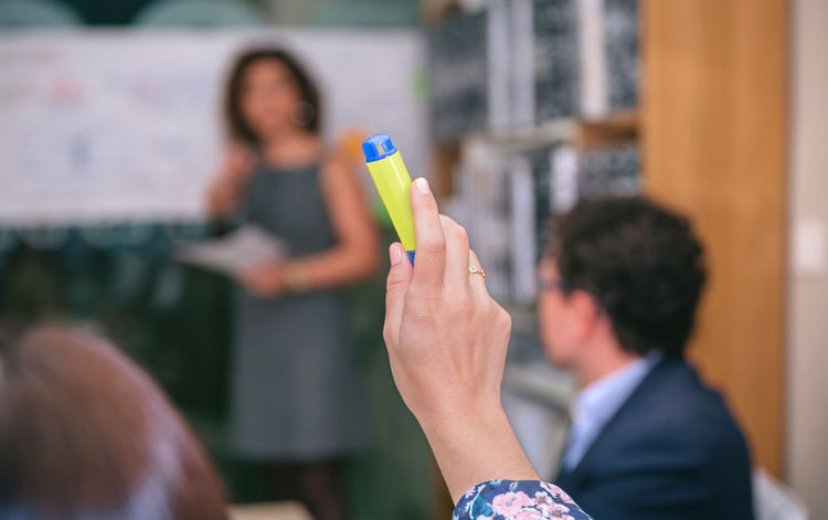 Close up of business woman raising her hand with highlighter to make question in a business meeting Business Coach Collaboration Horizontal Man Meeting Office Teamwork Woman Working Business Finance And Industry Businessman Businesswoman Coaching Colleague Communication Cooperation Group Of People Headquarters Management Profession Project Sucess Team Training