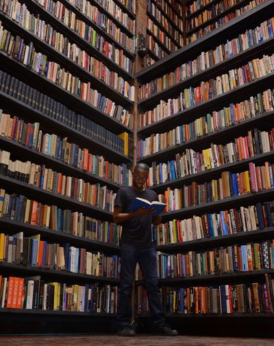 Low angle view of man reading book while standing by bookshelves in library