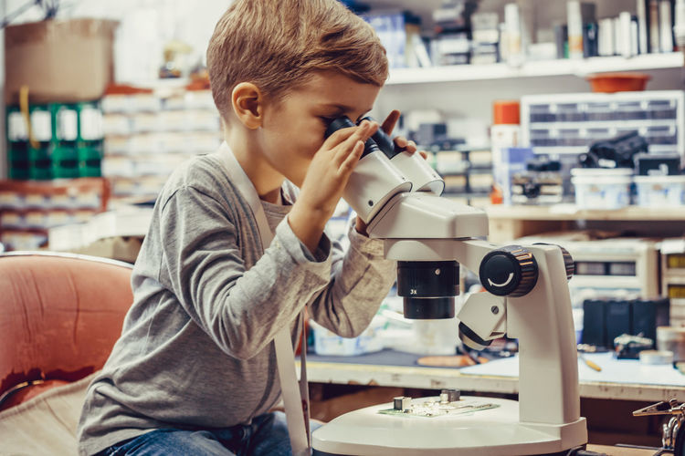 Small kid looking through microscope and analyzing circuit board in tech laboratory.