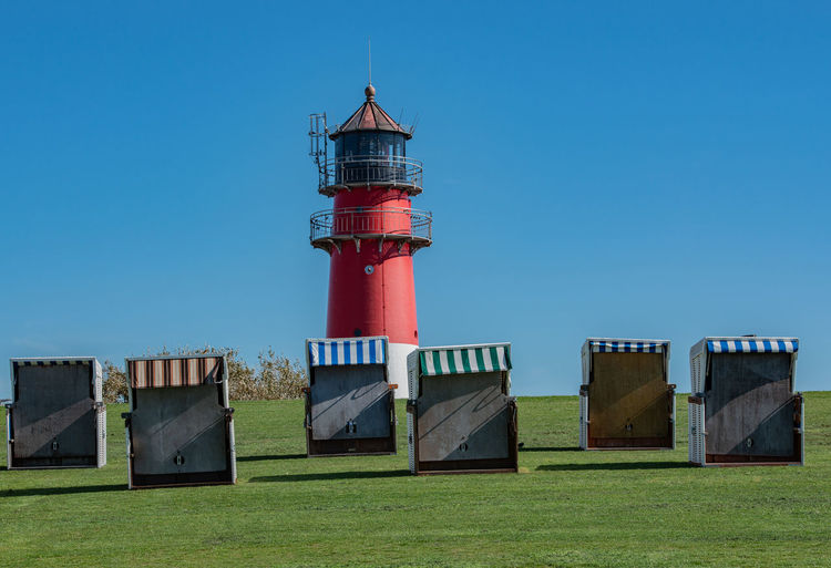 Hooded beach chairs and lighthouse on land against clear sky