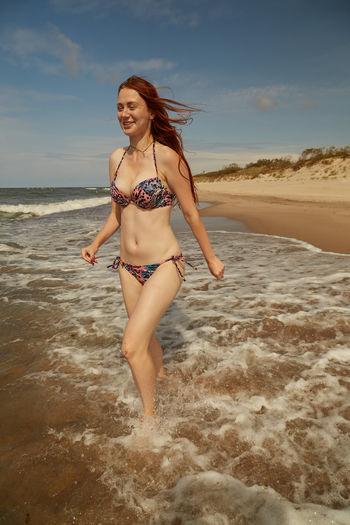 Smiling young woman walking at seashore