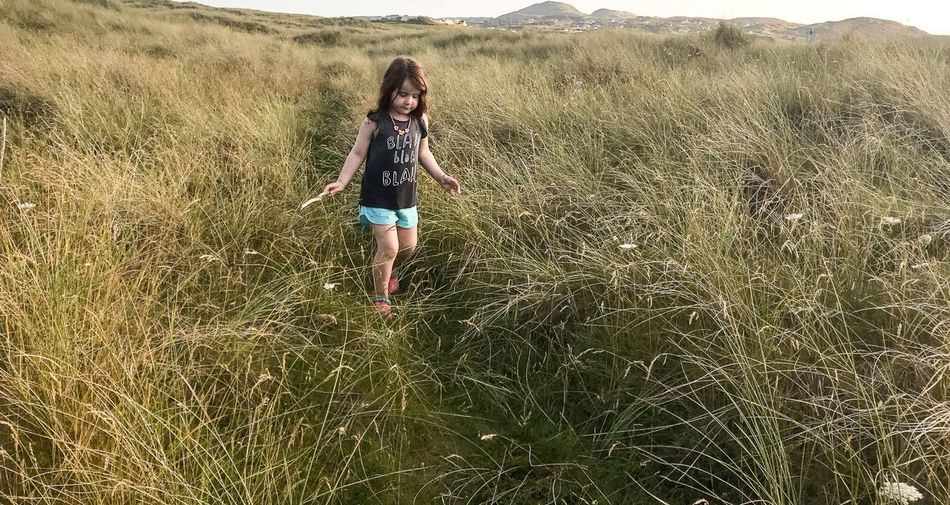 Full length of girl walking on grassy field
