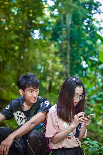 Woman using phone with boyfriend in forest
