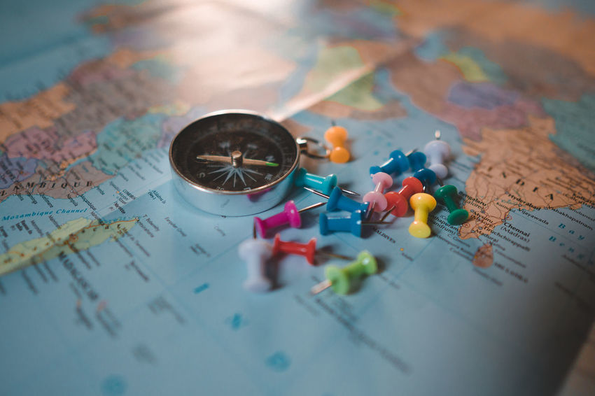 Compass on the map with pin marker around. Close-up Direction Discovery Exploration Guidance High Angle View Indoors  Map Multi Colored No People Physical Geography Planning Selective Focus Still Life Straight Pin Table Text Travel World Map