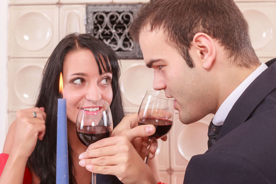 Romantic young couple toasting with red wine entwining their arms to sip from their glasses in a symbolic gesture of love, Celebration Couple Dating Dinner Entwined Glasses Hands Love Lovers Loving Red Relationship Romantic Toasting Canlelight Courting Emotion Feelings Men Party People Sweethearts Wine Women Young Adult