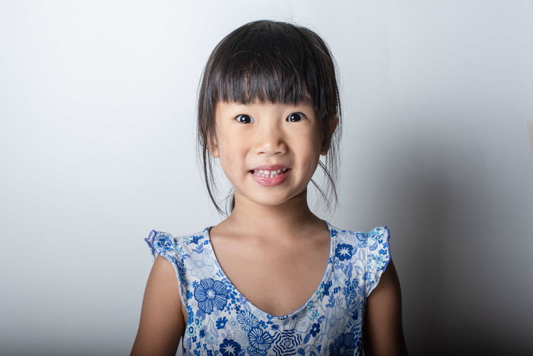 Portrait of smiling girl against white background