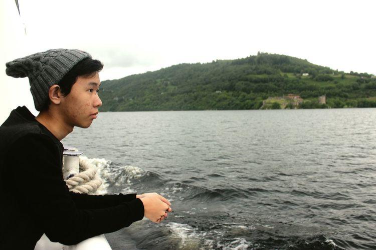 Side view of teenage boy looking at sea against sky