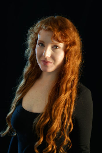 Black Background Redhead Beautiful Woman Black Background Close-up Curly Curly Hair Day Fair Skin Ginger Headshot Long Hair Looking At Camera Medium-length Hair One Person People Portrait Real People Red Hair Redhead Standing Studio Shot Young Adult Young Women