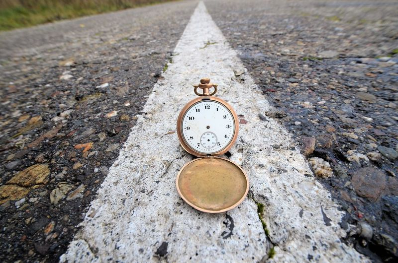 Close-up of clock on road
