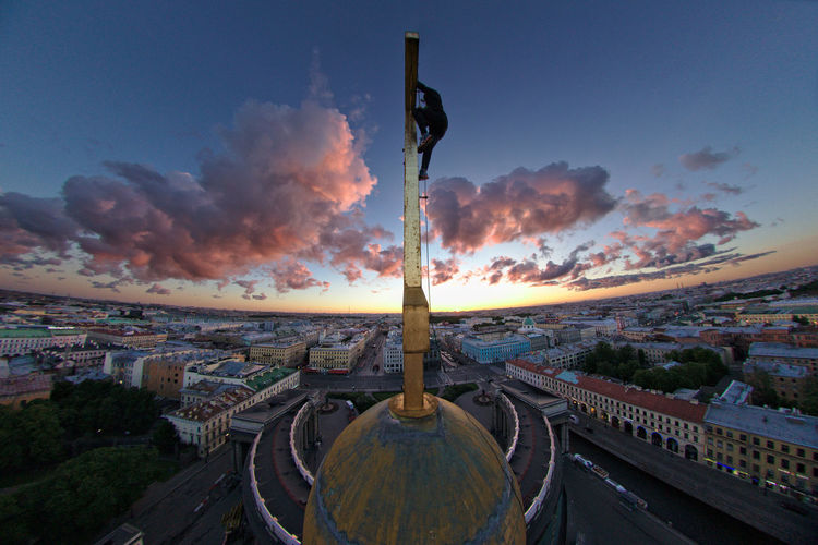 Silhouette Man Climbing On Cross Of Kazan Cathedral Against Sky