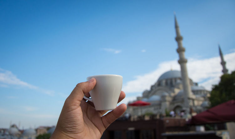 Architecture Building Exterior Built Structure City Close-up Coffee - Drink Coffee Cup Day Drink Focus On Foreground Food And Drink Holding Human Body Part Human Hand Leisure Activity Mosque One Person Outdoors Real People Refreshment Sky Tourism Travel Destinations Turkishcoffee Women