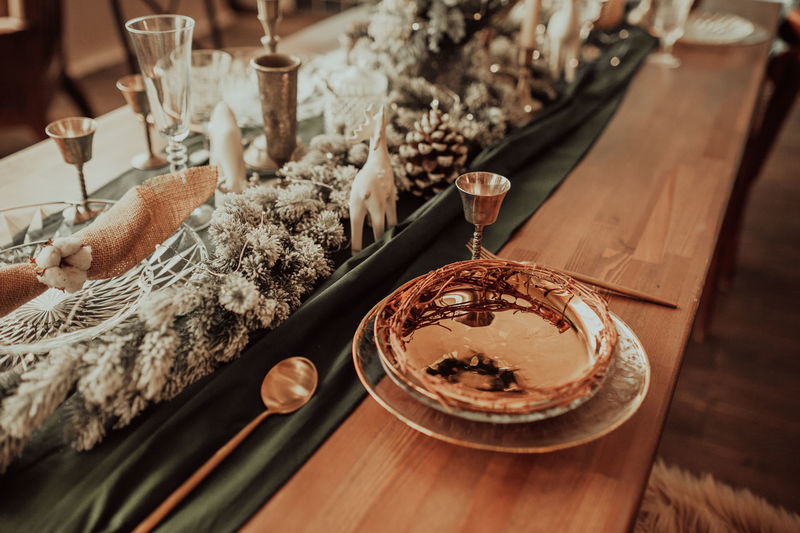 Style christmas table setting, gold plate and cutlery, on a wooden table and green cloth