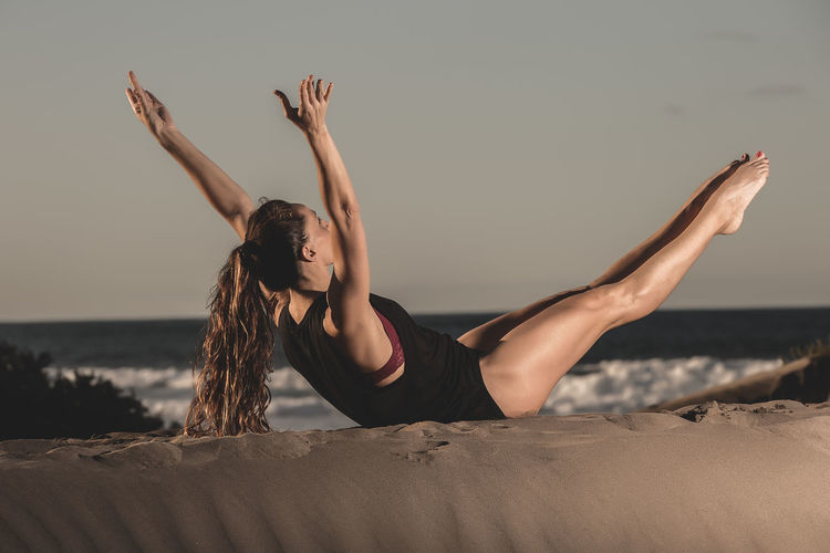 Woman with arms raised exercising at beach against sky
