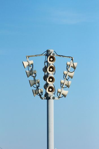 Low angle view of speakers against blue sky