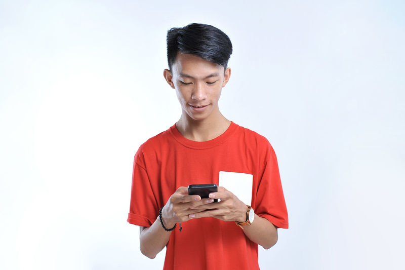 Low angle view of man using mobile phone against white background