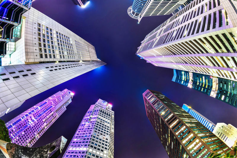 A bottom-up night view of a group of buildings in a business district in Singapore with fish eye lens Night Lights Singapore Architecture Building Building Exterior Built Structure City Financial District  Low Angle View Modern Night No People Office Building Exterior Raffles Place Skyscraper