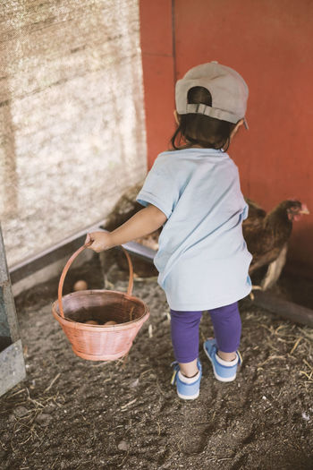 Rear View Of Girl Holding Basket At Poultry