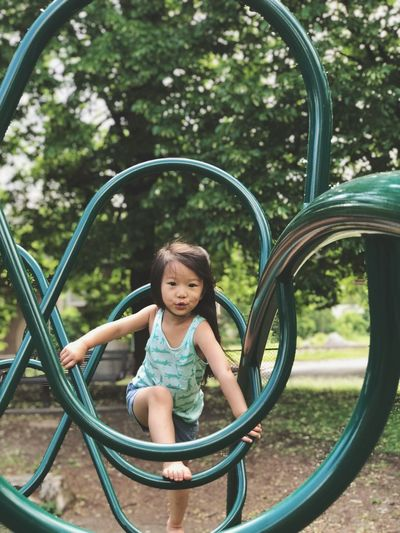 Portrait Of Girl Climbing On Green Play Equipment At Playground