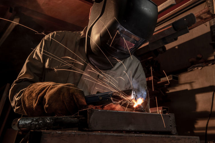 Working Metal Industry Industry Metal Occupation Indoors  Protective Workwear Factory Motion One Person Heat - Temperature Men Protection Welding Real People Blurred Motion Business Skill  Expertise Sparks Preparation  Industrial Equipment