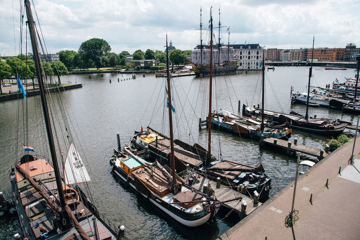 Old sailing ships moored in Amsterdam Amsterdam Architecture Building Exterior Canals Cloud - Sky Day Gondola - Traditional Boat Harbor Mast Mode Of Transport Moored Nautical Vessel No People Outdoors Sailboat Sailing Ships Sky Tall Ship Transportation Travel Destinations Water