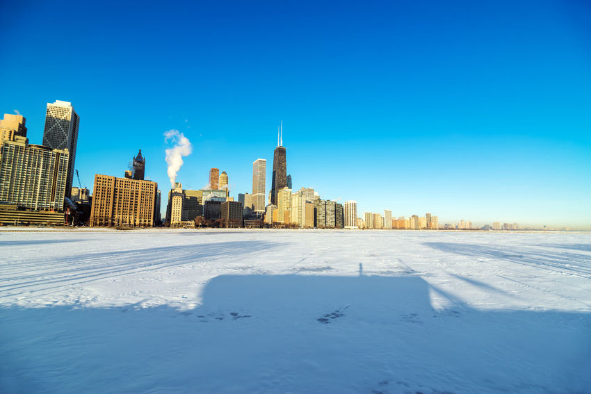 View of the Chicago skyline with frozen and snowy Lake Michigan visible in the foreground Architecture Blue Building Chicago City Cityscape Color Contemporany Destination Donwtown Downtown Dusk Illinois Outdoors Scene Skycraper Skyline Skyscraper Structure Towers Travel United States Urban USA Winter