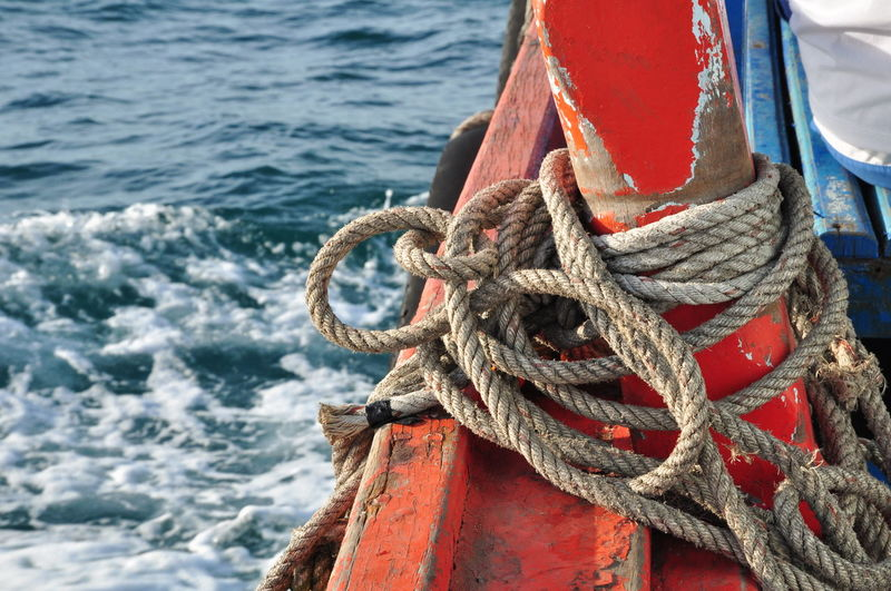 Close-up of rope tied to boat moored in sea