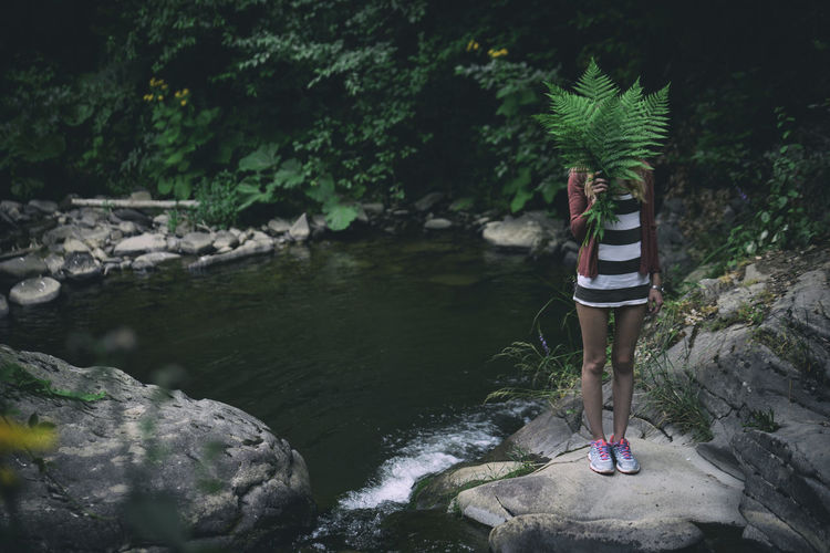 Woman Holding Fern While Standing On Rock By Pond In Forest