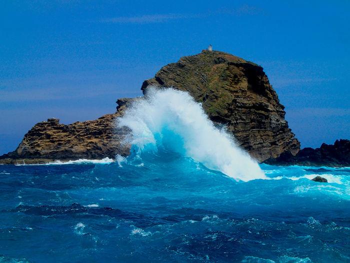 Sea waves splashing on rocks against clear blue sky